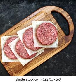 Hausgemachte Schweinekoteletts auf Holzbrett, Draufsicht. Rohes Rindfleisch aus Rind, Steak Burgers Cutlets auf schwarzem Tischhintergrund, Draufsicht. Bauern, die nicht gekochte Rindsburger zum Grillen oder Frittieren im Grill haben.