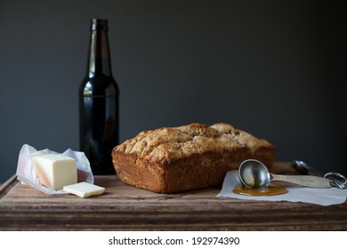 Homemade beer bread with honey and butter on cutting board