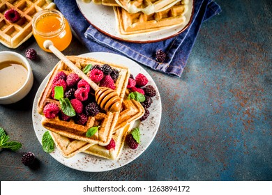 Homemade belgian waffles with berries and honey, on dark blue background copy space
