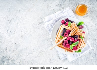 Homemade belgian waffles with berries and honey, on a concrete background copy space