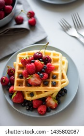Homemade Belgian waffles with berries on gray table. Healthy breakfast concept.