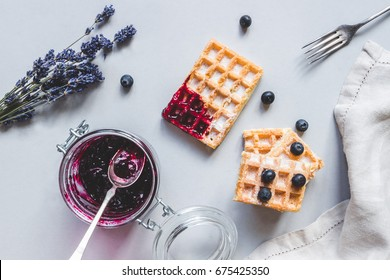 Homemade belgian waffles with blueberries and jam on the light blue table.