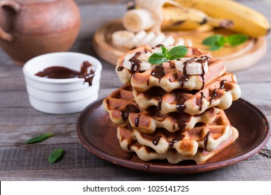 Homemade Belgian waffles with chocolate sauce and banana slice