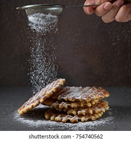 Homemade Belgian waffles, on top of poured sifting of powdered sugar on black concrete background