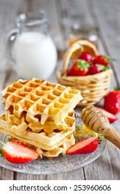 Homemade belgian waffles with ripe strawberry, honey and milk on wooden background