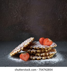 Homemade Belgian waffles with strawberry and powdered sugar on black concrete background