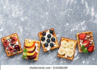 Homemade Belgian waffles with a variety of fruits on a gray background. Top view, copy space