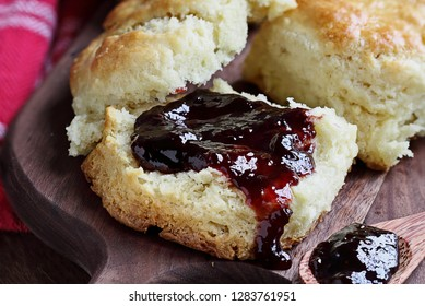 Homemade berry preserves dripping over fresh buttermilk southern biscuits or scones over rustic cutting board background.
