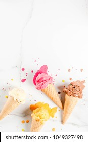 Homemade berry vanilla caramel chocolate ice cream in waffle cones, white marble background copy space top view