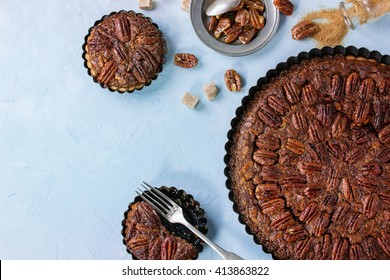 Homemade Big round caramel pecan pie and small tartlets in black iron forms, served with brown sugar, caramel sauce and vintage cutlery over blue textured background. Flat lay with copy space
