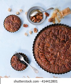 Homemade Big round caramel pecan pie and small tartlets in black iron forms, served with brown sugar, caramel sauce and vintage cutlery over blue textured background. Flat lay, square image