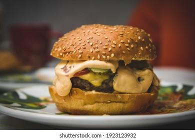 homemade big tasty burger. A yummy burger on a plate, homemade fast food . A big tasty burger.