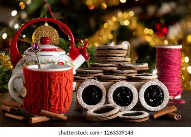 Homemade biscuits with bluebrry jam served with tea in Christmas atmosphere with decorated tree in the background.