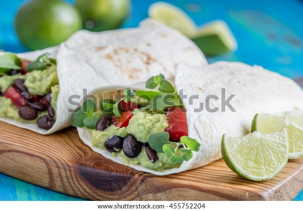 Homemade black bean and avocado burrito with tomatoes,  Mexican food, vegan