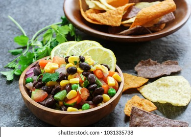 Homemade black bean corn salsa with chips served in a wooden bowl, selective focus