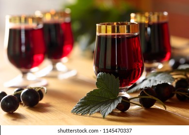 Homemade black currant liqueur and fresh berries, wooden background.