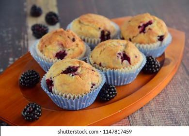 Homemade blackberry muffins in paper cups, selective focus