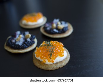 Homemade blinis with black and orange fish eggs, dill, onions and cream isolated on black background