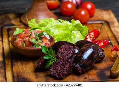 Homemade blood sausage prieta de sangre with tomato sauce salsa, lettuce on wooden board