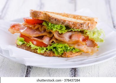 Homemade BLT Sandwich with Bacon Lettuce and Tomato on white wooden background