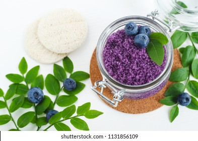 Homemade blueberry face and body sugar scrub/bath salts/foot soak in a glass jar. DIY cosmetics for natural skin care. Top view, copy space.