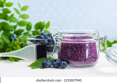 Homemade blueberry face and body sugar scrub/bath salts/foot soak in a glass jar. DIY cosmetics for natural skin care. Copy space.