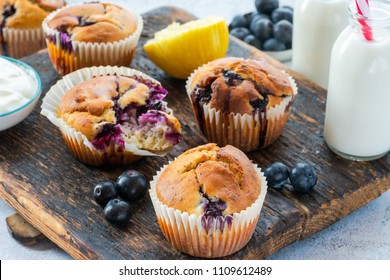 Homemade blueberry and lemon muffins on wooden board