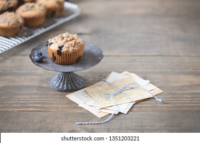 Homemade Blueberry Muffin Isolated on Tin Pedestal on Wooden Table Top; Vintage Recipe Cards; Cooling Rack of Muffins in Background