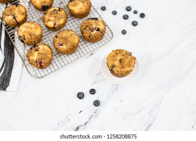 homemade blueberry muffins on wire rack on white and gray marble countertop; one isolated in front