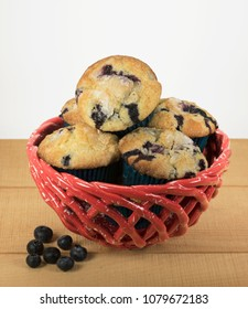 Homemade blueberry muffins piled in a red and white ceramic basket and loose blueberries are on a wooden table with a white background.