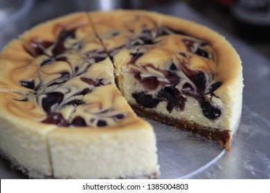 Homemade blueberry New York cheesecake based with Lotus cookie curst and cheesecake made of creamcheese, mascarpone cheese, sugar and egg without flour. On the top of cake put blueberry jam and swirl
