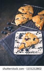 Homemade Blueberry Scones on Bon Appetite Plates, Dark Blue Napkin, Fresh Blueberries Scattered Around, Black Background, More Scones in Background on Wire Rack