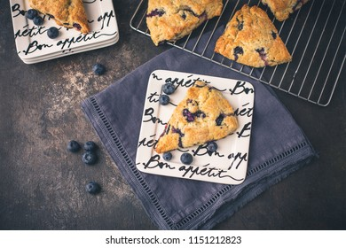 Homemade Blueberry Scones on Bon Appetite Plates, Dark Blue Napkin, Fresh Blueberries Scattered Around, Black Background, More Scones in Background on Wire Rack