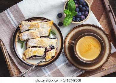 Homemade blueberry strudel, on wooden tray.