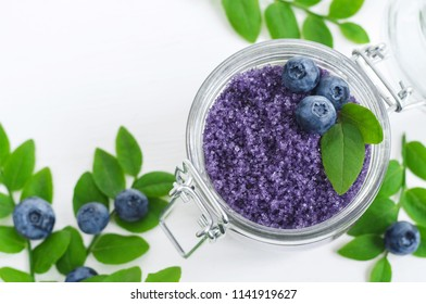 Homemade blueberry sugar scrub/bath salts/foot soak in a glass jar. DIY cosmetics for natural skin care. Top view, copy space.