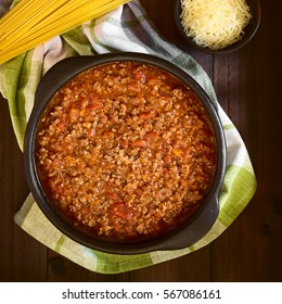 Homemade bolognese sauce made of fresh tomato, onion, carrot, garlic and mincemeat served in rustic bowl, uncooked spaghetti and grated cheese on the side, photographed overhead with natural light