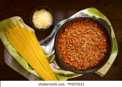 Homemade bolognese sauce made of fresh tomatoes, onion, carrot, garlic and mincemeat served in rustic bowl, uncooked spaghetti and grated cheese on the side, photographed overhead with natural light
