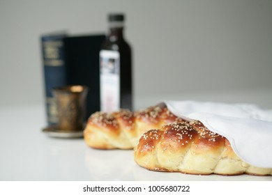 Homemade braided challah for Shabbat with a glass of wine and book