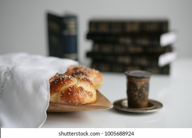 Homemade braided challah for Shabbat with a glass of wine and books