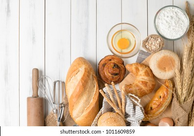 Homemade bread or bakery with fresh egg, flour and bakery equipment on white wood background