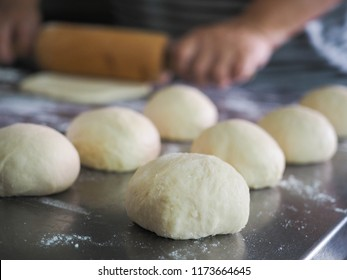 Homemade bread making : bread roll dough on table and baker rolling dough in background