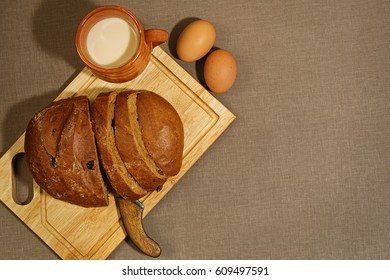 Homemade bread with raisins, baked milk and baked eggs on the rude textile background