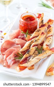 Homemade bread sticks with smoked cured ham served as an appetizer with slices of ham and wine on a white plate