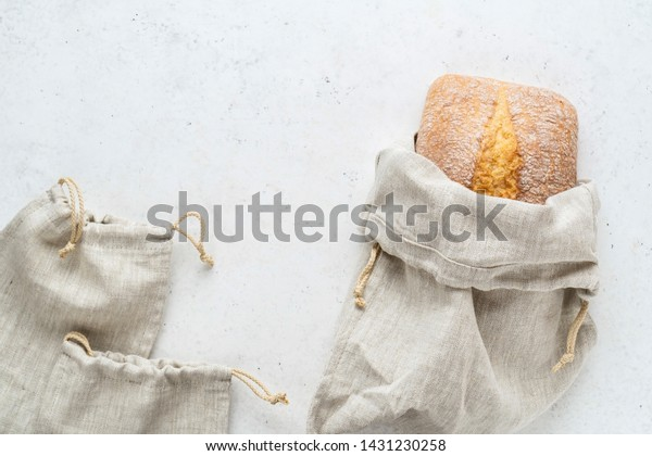 Homemade bread stored in a reusable linen bag with drawstring. Eco friendly Zero waste concept. White stone background. Top view copy space.