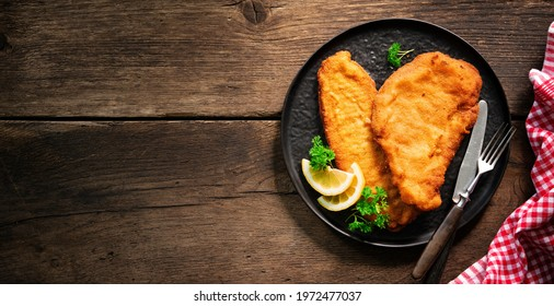 Homemade breaded wiener schnitzel served with parsley and lemon slices on dark wooden table
