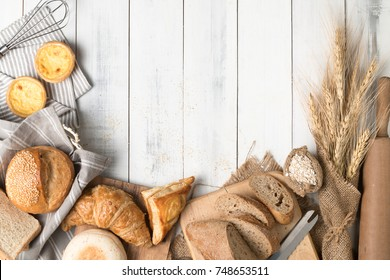 Homemade breads or bun, croissant and bakery ingredients on white wood background, breakfast food concept top view and copy space