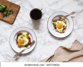 Homemade breakfast eggs with bacon on a white plates with coffee served on a white marble table surface with coffee and cloth