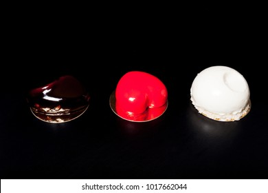 Homemade bright mousse cakes with mirror glaze on a black background. Toned.