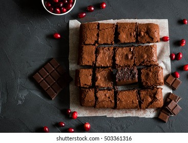 Homemade brownies with dark chocolate and cranberries on dark background. Overhead shot.