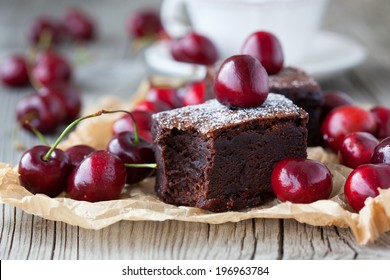 Homemade brownies with fresh berry and cup of tea on old wooden background, selective focus